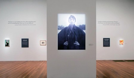 A gallery shot featuring an imposing portrait of Georgia O'Keeffe blown up and looking down on the gallery formidably