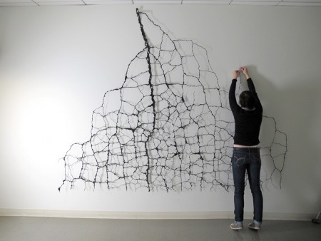 A conservator installing the web-like construction by Mattew Picton