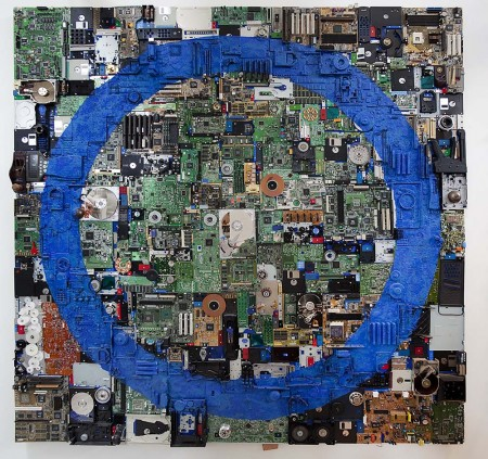 An abstract work made of computer parts with a large blue circle domination the picture plane
