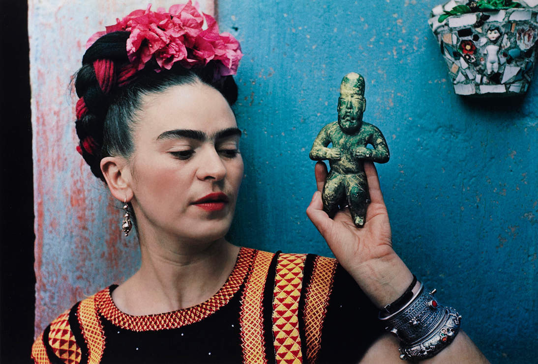"""Nickolas Muray, """"Frida with Olmeca Figurine, Coyoacán,"""" 1939. Color carbon print, 10 3/4 x 15 3/4 in. (27.3 x 40 cm). Fine Arts Museums of San Francisco, Gift of George and Marie Hecksher in honor of the tenth anniversary of the new de Young museum. 2018.68.1. © Nickolas Muray Photo Archives"""