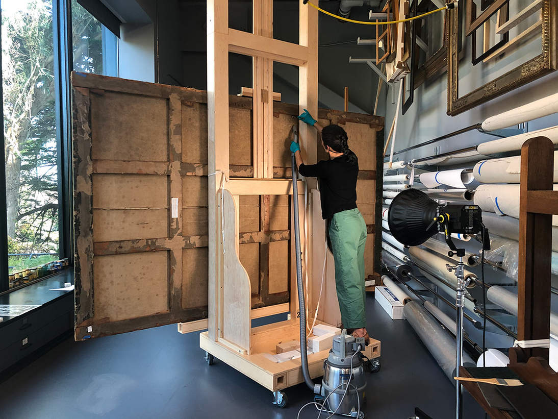 Kathryn Harada dusts the back of the work  in the Paintings Conservation Studio