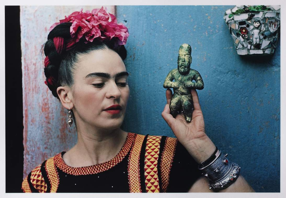 "Nickolas Muray, ""Frida with Olmeca Figurine, Coyoacán,"" 1939. Color carbon print, 10 3/4 x 15 3/4 in. (27.3 x 40 cm). Fine Arts Museums of San Francisco, Gift of George and Marie Hecksher in honor of the tenth anniversary of the new de Young museum, 2018.68.1 © Nickolas Muray Photo Archives"
