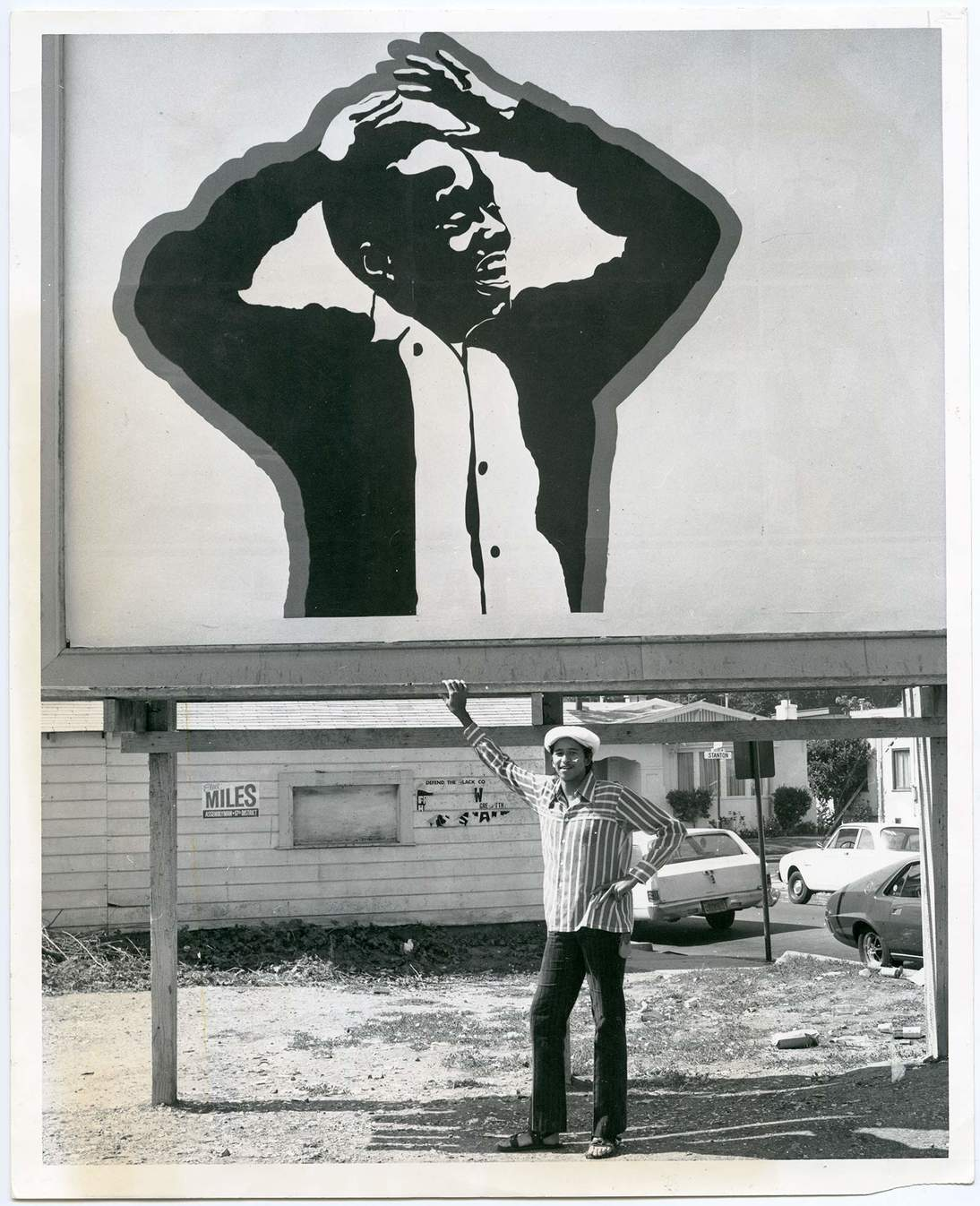 Cleveland Bellow photographed standing under his billboard, Oakland Post Photograph Collection, MS 169, African American Museum and Library at Oakland, Oakland Public Library