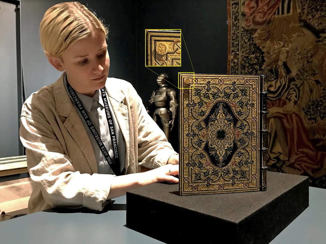 Madison Brockman adjusts the distance between the two openings displayed from The Selected Poems of William Morris. Highlighted on the back cover is one of the disguised rare earth magnets used to hold the book open. This magnet is covered with paper that has the cover's design printed on it (detail).