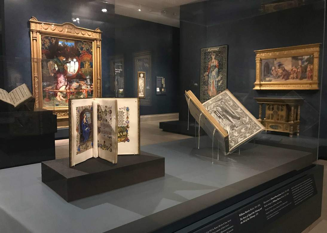 "Gallery view of ""Truth and Beauty"" at the Legion of Honor. The case in the foreground houses ""The Selected Poems of William Morris"" whose minimally-visible upright mounting system allows for more visibility than a traditional book cradle, seen supporting the other two books in the image."